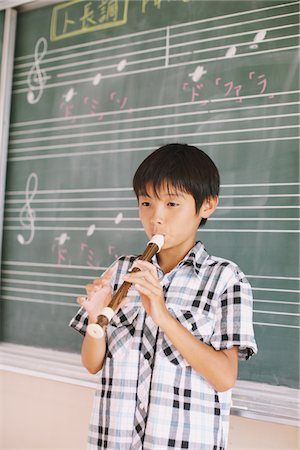 Japanese Boy Playing Flute In Front Chalkboard Stock Photo - Rights-Managed, Code: 859-03860843
