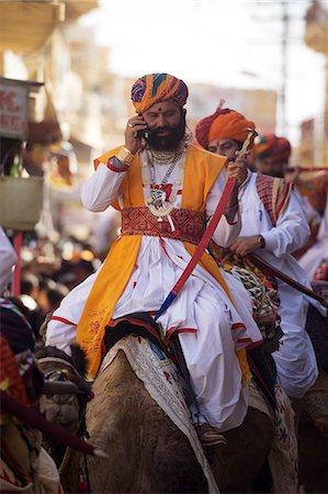rajasthan camel - Man riding camel using cell phone at Jaisalmer festival,Rajasthan,India Stock Photo - Rights-Managed, Code: 851-02960457