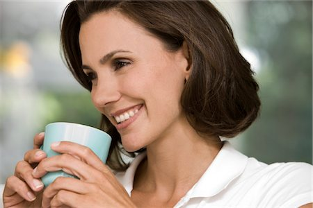 Smiling woman holding cup of coffee Stock Photo - Rights-Managed, Code: 853-05523410