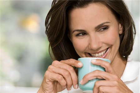 Smiling woman holding cup of coffee Stock Photo - Rights-Managed, Code: 853-05523411
