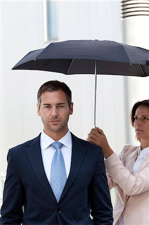 Businesswoman holding umbrella above businessman Stock Photo - Rights-Managed, Code: 853-06441695