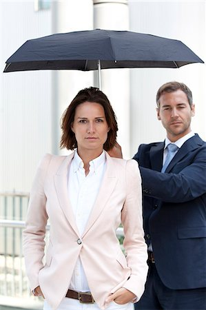 Businessman holding umbrella above businesswoman Stock Photo - Rights-Managed, Code: 853-06441697