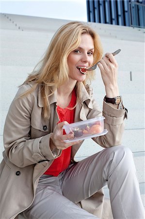 Blond woman having a snack on stairs Stock Photo - Rights-Managed, Code: 853-06441745