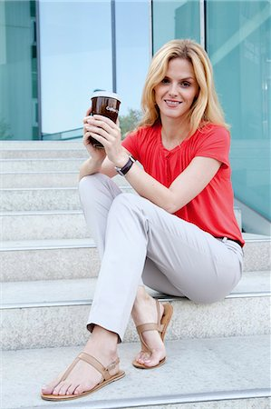 Blond woman with coffee to go on stairs Stock Photo - Rights-Managed, Code: 853-06441761