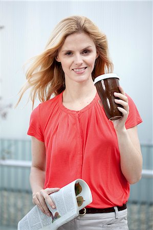 Smiling blond woman holding coffee to go and newspaper Stock Photo - Rights-Managed, Code: 853-06441776