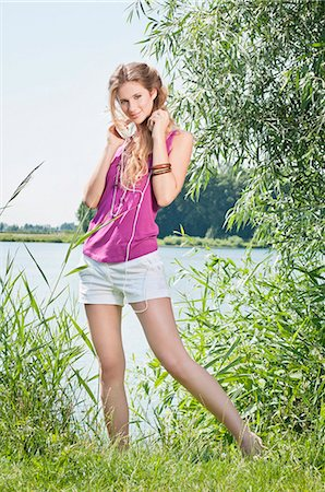 Blond young woman listening to music at a lake Stock Photo - Rights-Managed, Code: 853-06442057