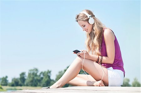 Blond young woman with headphones on a jetty at a lake Stock Photo - Rights-Managed, Code: 853-06442067