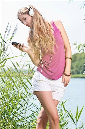 Blond young woman listening to music at a lake Stock Photo - Rights-Managed, Code: 853-06442062