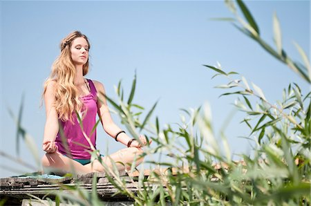Blond young woman practicing yoga at a lake Stock Photo - Rights-Managed, Code: 853-06442077
