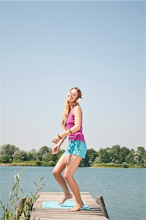 Blond young woman listening to music at a lake Stock Photo - Rights-Managed, Code: 853-06442078