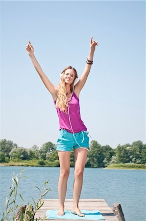 Blond young woman listening to music at a lake Stock Photo - Rights-Managed, Code: 853-06442079