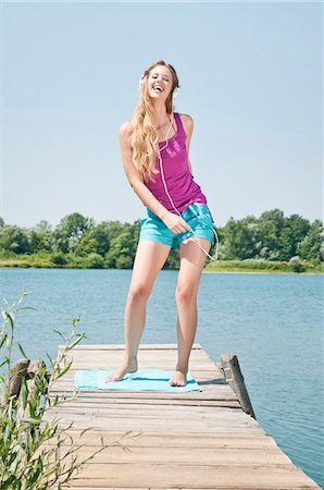 Blond young woman listening to music at a lake Stock Photo - Rights-Managed, Code: 853-06442080
