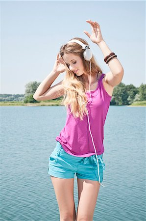 Blond young woman listening to music at a lake Stock Photo - Rights-Managed, Code: 853-06442081