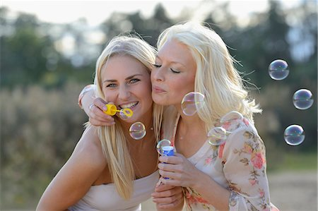 Two happy young blond women blowing soap bubbles outdoors Stock Photo - Rights-Managed, Code: 853-06442225
