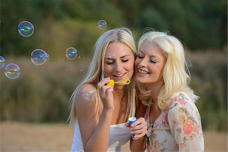 Two happy young blond women blowing soap bubbles outdoors Stock Photo - Rights-Managed, Code: 853-06442227