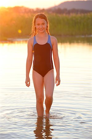 preteen swimsuit - Girl standing in the shallow water of a lake Stock Photo - Rights-Managed, Code: 853-07148641