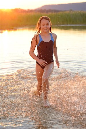 preteen swimsuit - Girl running in the shallow water of a lake Stock Photo - Rights-Managed, Code: 853-07148642
