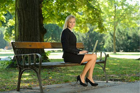 people sitting on bench - Young blond business woman with laptop in a park Stock Photo - Rights-Managed, Code: 853-07241821