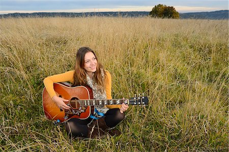 Smiling young woman playing guitar in field Stock Photo - Rights-Managed, Code: 853-07241903