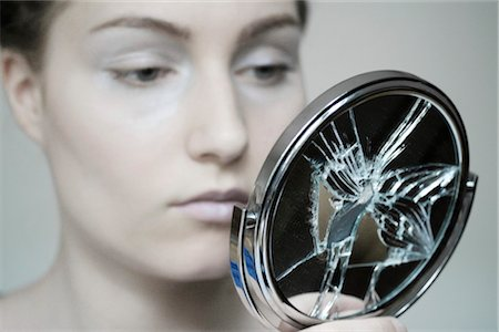 woman looking into a broken mirror, portrait Stock Photo - Rights-Managed, Code: 853-02913543