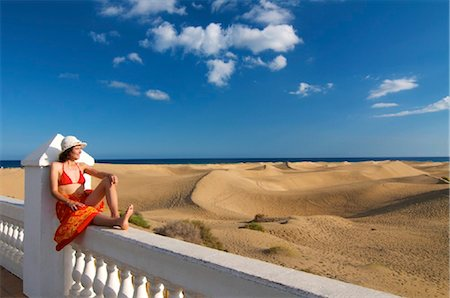 Woman sitting on a fence looking at the sand dunes, Maspalomas, Gran Canaria, Spain Foto de stock - Con derechos protegidos, Código: 853-03227826