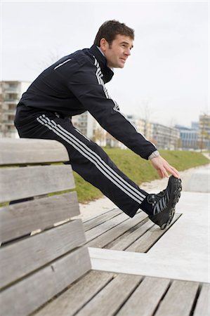 Jogger making warm-up exercises, side view Stock Photo - Rights-Managed, Code: 853-03458832