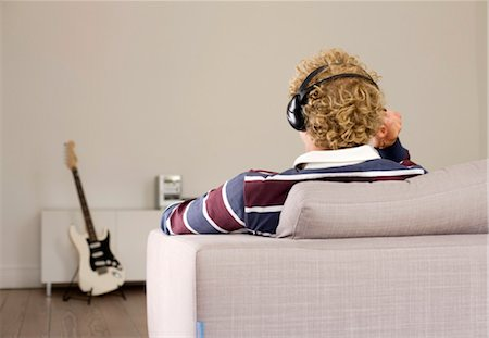 Man with headphones sitting on a couch, e-guitar in the background, rear view Stock Photo - Rights-Managed, Code: 853-03459095
