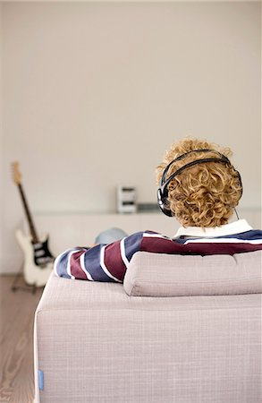 Man with headphones sitting on a couch, e-guitar in the background, rear view Stock Photo - Rights-Managed, Code: 853-03459093