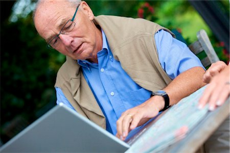 Senior man with laptop and road map, close-up Stock Photo - Rights-Managed, Code: 853-03616989