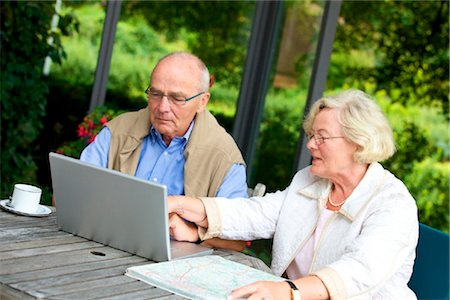 Senior couple on terrace with laptop and road map Stock Photo - Rights-Managed, Code: 853-03616991