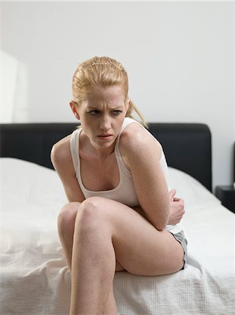 Young woman sitting on bed Stock Photo - Rights-Managed, Code: 853-03776367