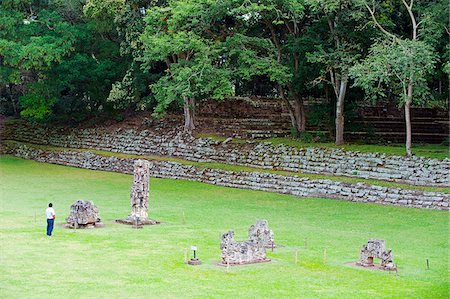 Central America, Honduras, Copan Ruins, Mayan archeological site, Copan Ruins, Unesco World Heritage site; tourist looking at ruined statues Stock Photo - Rights-Managed, Code: 862-05997858