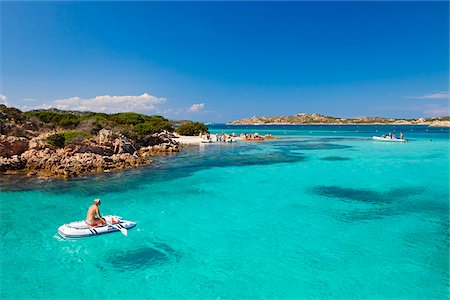 Italy, Sardinia, Olbia-Tempo, La Maddalena Archipelago. A woman sits on a boat  next to Budelli Island. Stock Photo - Rights-Managed, Code: 862-05998243