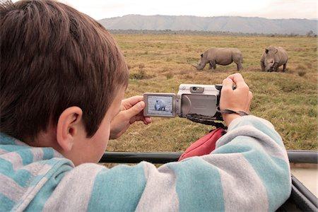 Boy photographing white rhino from a vehicle in Oserian Wildlife Sanctuary, near Lake Naivasha, Kenya. Stock Photo - Rights-Managed, Code: 862-05998399