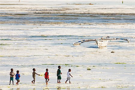 simsearch:400-04638538,k - Tanzania, Zanzibar, Unguja, Jambiani. A group of boys walk along the beach at low tide. Stock Photo - Rights-Managed, Code: 862-05999581