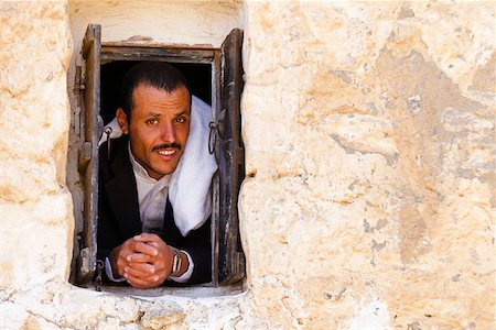 Yemen, Sana'a Province, Haraz Mountains, Al Hajjarah. A man looks out from a window. Stock Photo - Rights-Managed, Code: 862-05999734