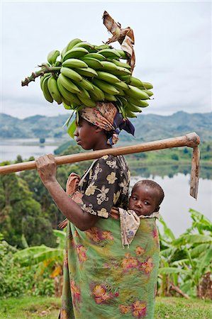 A Ugandan woman returns from her farm with bananas balanced on her head, her child slung comfortably on her back, Uganda, Africa Stock Photo - Rights-Managed, Code: 862-06543270