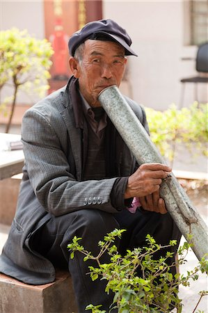 China, Yunnan, Xinping. An elderly man enjoying a peaceful smoke. Stock Photo - Rights-Managed, Code: 862-06676235