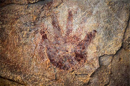 Chad, Elikeo, Ennedi, Sahara. A handprint on a cave wall superimposing earlier white artwork. Probably early Pastoral Period. Stock Photo - Rights-Managed, Code: 862-06676416