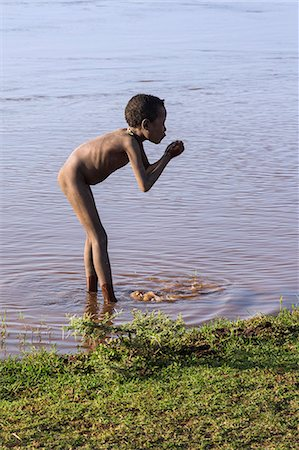 A young Dassanech boy drinks muddy water from the Omo River, Ethiopia Stock Photo - Rights-Managed, Code: 862-06676697