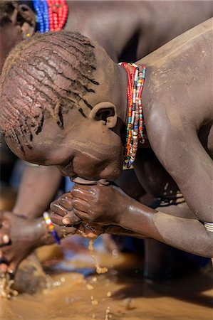 A young Dassanech girl drinking dirty water from the Omo River, Ethiopia Stock Photo - Rights-Managed, Code: 862-06676726