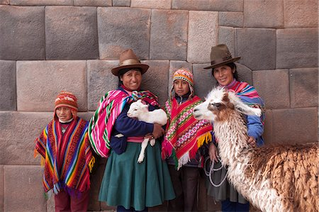 south american woman - South America, Peru, Cusco. Quechua people standing in front of an Inca wall, holding a lamb and a llama and wearing traditional clothing including a bowler hat, liclla, chullo and poncho    while talking on a cell phone in the UNESCO World Heritage listed former Inca capital of Cusc Stock Photo - Rights-Managed, Code: 862-06677338