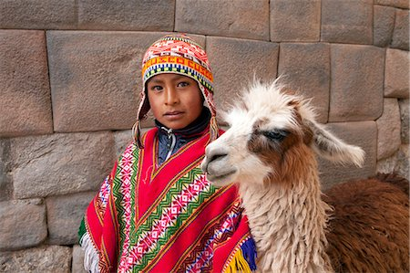peru and culture - South America, Peru, Cusco. A Quechua boy in a poncho and a chullo woollen cap with a Llama standing in front of an Inca wall in the UNESCO World Heritage listed former Inca capital of Cusco Stock Photo - Rights-Managed, Code: 862-06677339