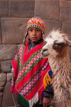 peru and culture - South America, Peru, Cusco. A Quechua boy in a poncho and a chullo woollen cap with a Llama standing in front of an Inca wall in the UNESCO World Heritage listed former Inca capital of Cusco Stock Photo - Rights-Managed, Code: 862-06677340