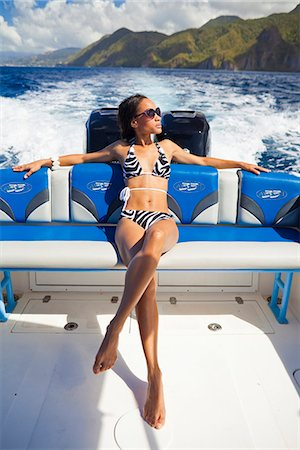 Dominica, Soufriere. A young woman sunbathes on the back of a Powerboat near Soufriere. (MR). Stock Photo - Rights-Managed, Code: 862-06825274