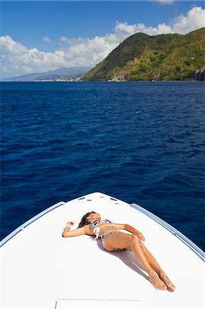 Dominica, Soufriere. A young woman sunbathes on the foredeck of a Powerboat near Soufriere. (MR). Stock Photo - Rights-Managed, Code: 862-06825276