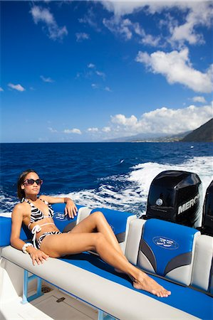 Dominica, Soufriere. A young woman sunbathes on the back of a Powerboat near Soufriere. (MR). Stock Photo - Rights-Managed, Code: 862-06825273