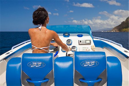 Dominica, Soufriere. A young woman at the helm of a  Powerboat near Soufriere. (MR). Stock Photo - Rights-Managed, Code: 862-06825282