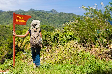 Dominica, Riviere Cyrique. A young woman stands by a sign at the start of the trail to Wavine Cyrique. (MR). Stock Photo - Rights-Managed, Code: 862-06825301