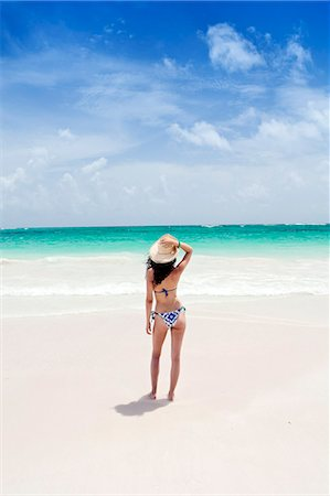 Caribbean, Dominican Republic, La Altagracia province, Punta Cana, Bavaro, Beautiful young woman shot from behind wearing a beach hat and a bikini on the beach facing a turquoise Atlantic (MR) Stock Photo - Rights-Managed, Code: 862-07495891